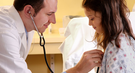 Doctor using a stethoscope on a patient